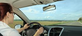 Kvinde kører bil med åbent vindue
