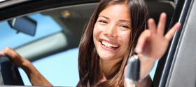 Glad pige viser stolt bilnøgler frem, efter hun har bestået køreprøven